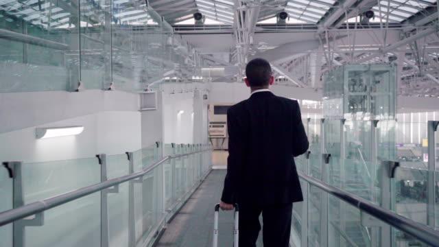 geschäftsmann mit einem blauen koffer, gehen sie zum check-in-schalter airline airport. - lebensweg stock-videos und b-roll-filmmaterial