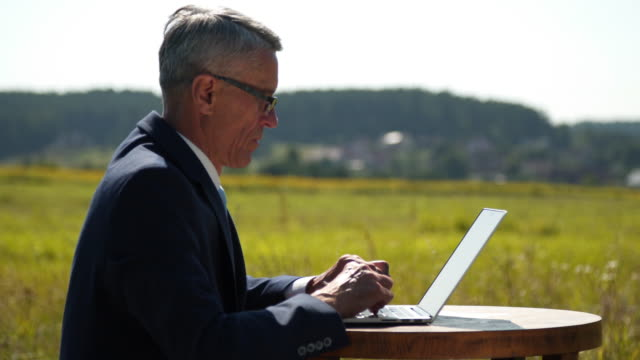 Businessman with a computer on the field