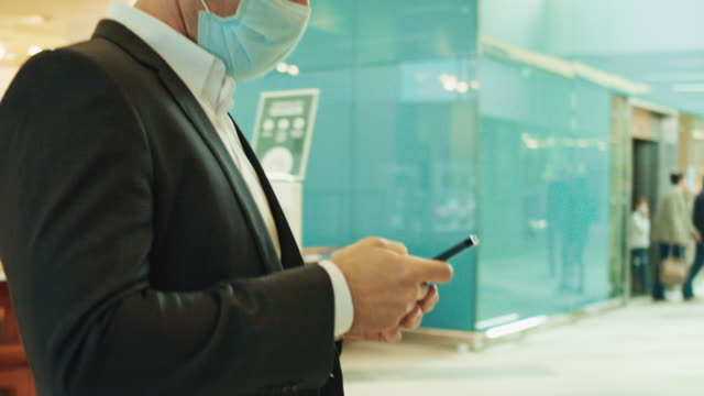 slo mo businessman with a mask using a smartphone in contemporary office hallway - place of work stock videos & royalty-free footage
