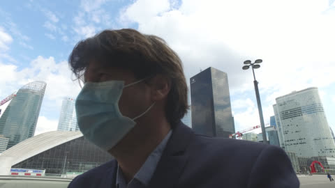 businessman with a protective mask in a business district. paris april 27 during the lockdow, the man continues to go to work in the business... - businesswear stock videos & royalty-free footage