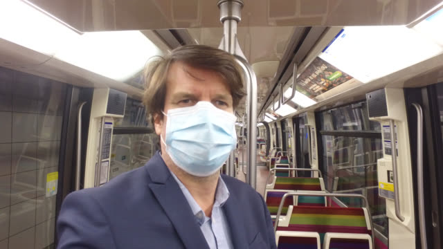 businessman with a protective mask in the subway train to go to work. paris april 27 during the lockdow, the man continues to go to work in the... - île de france stock-videos und b-roll-filmmaterial