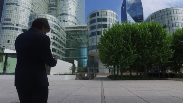 businessman with a protective mask walking on the street, in a business district. paris april 27 during the lockdow, the man continues to go to work... - businesswear stock videos & royalty-free footage
