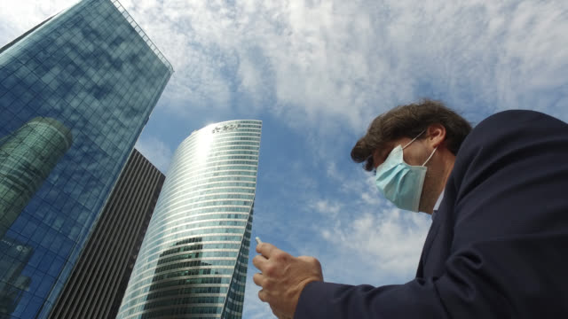 businessman with a protective mask, with a phone. paris april 27 during the lockdow, the man continues to go to work in the business district of... - businesswear stock videos & royalty-free footage