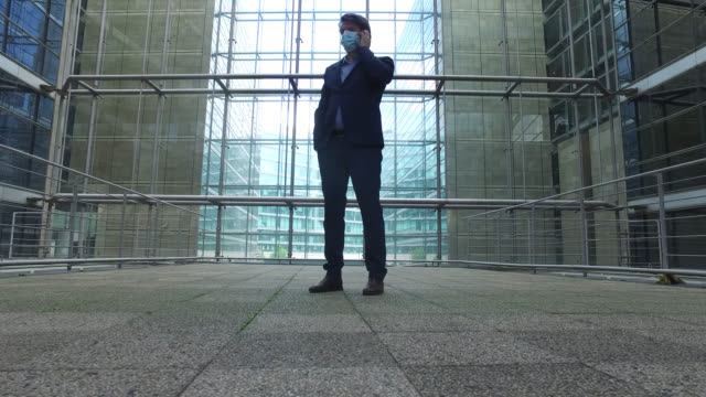 businessman with a protective mask, with a phone. paris april 27 during the lockdow, the man continues to go to work in the business district of... - île de france stock-videos und b-roll-filmmaterial