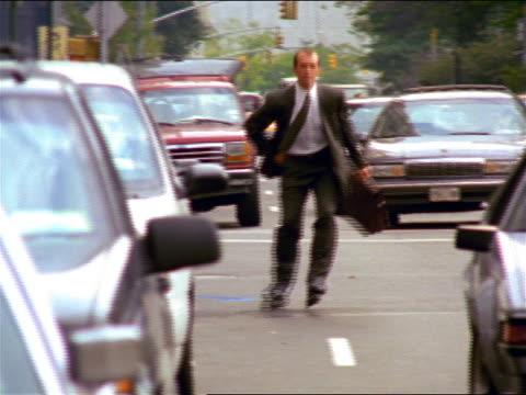 vídeos de stock, filmes e b-roll de businessman with briefcase inline skating in traffic towards camera on city street / nyc - 1990 1999
