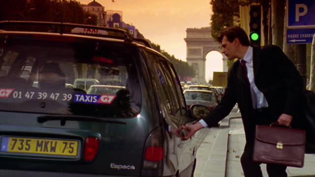 Businessman with briefcase + luggage entering taxi on Champs Elysee with Arc de Triomphe in background