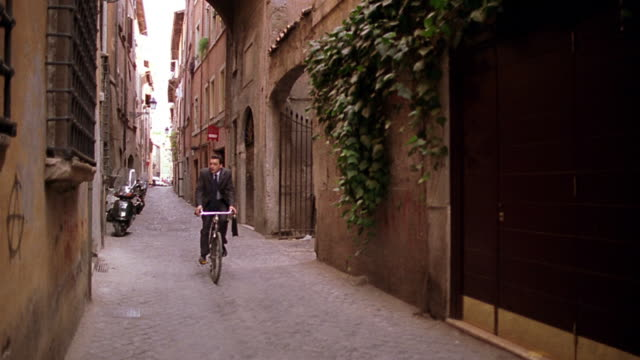 Businessman with briefcase riding bicycle toward + past camera on narrow street / Rome, Italy