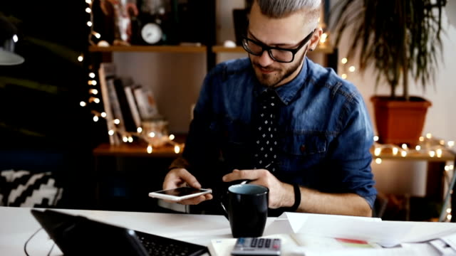 Businessman with cell phone and paperwork writing at desk