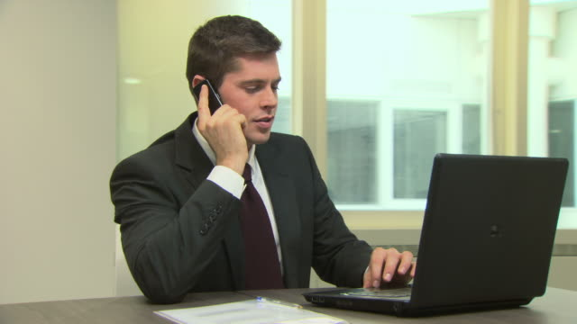 Businessman with cellphone and laptop, dolly shot