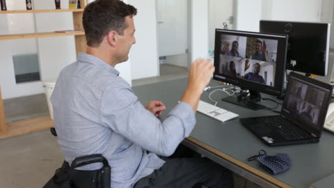 businessman with disability on wheelchair having a video conference at his desk - disability stock videos & royalty-free footage