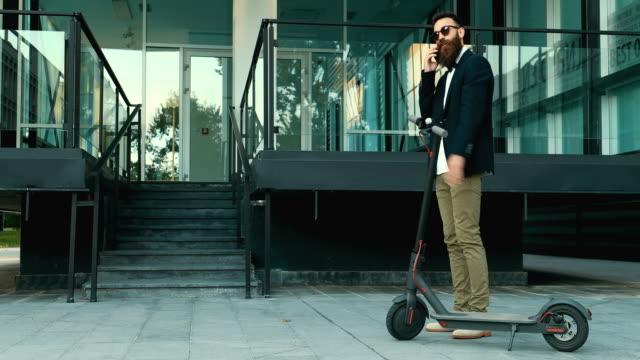 geschäftsmann mit elektro-push-scooter - motorroller stock-videos und b-roll-filmmaterial