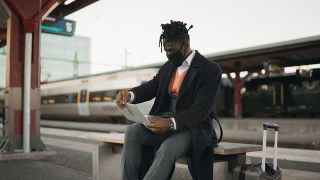 vidéos et rushes de homme d'affaires avec le masque facial utilisant son ordinateur portatif à la station - quai de gare