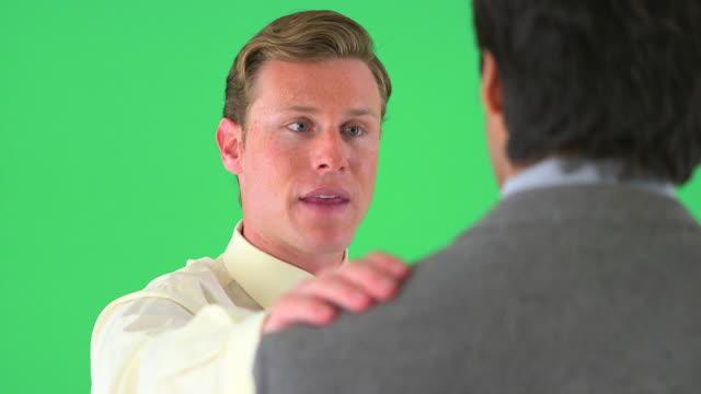 businessman with hand on colleagues' shoulder on greenscreen - 全套西裝 個影片檔及 b 捲影像