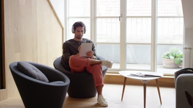 vídeos de stock e filmes b-roll de businessman with headphones using digital tablet - de corpo inteiro