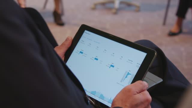 vídeos y material grabado en eventos de stock de empresario con informe infográfico en tablet pc - sección del medio