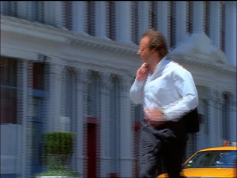 PAN businessman with jacket over shoulder running on NYC street