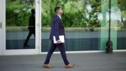 Businessman with laptop walking on street