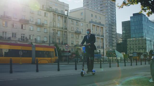 vídeos y material grabado en eventos de stock de hombre de negocios con máscara de montar scooter en el centro de la ciudad. transporte seguro durante la pandemia - ciclomotor vehículo de motor