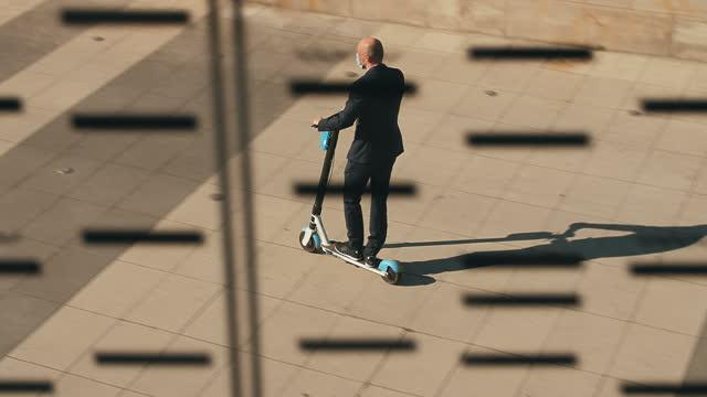 vídeos y material grabado en eventos de stock de hombre de negocios con máscara montando scooter en bulevares. transporte seguro en la ciudad - ciclomotor vehículo de motor