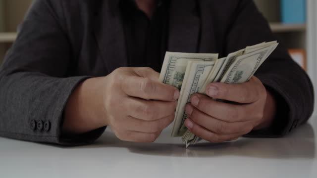 geschäftsmann mit geld in der hand. geld zählen - bestechung stock-videos und b-roll-filmmaterial