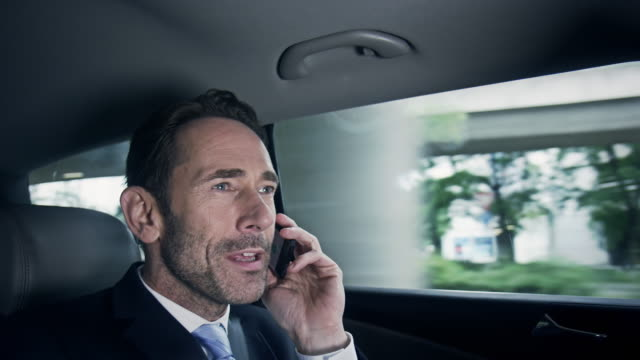 businessman with phone in car - chauffeur stock videos and b-roll footage