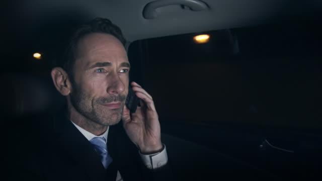 uomo d'affari con telefono in auto - urgenza video stock e b–roll