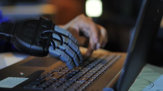 stockvideo's en b-roll-footage met zakenman met prothese met de hand te typen op de computer toetsenbord. jonge man met een cyborg hand werken op laptop. protheses - ledematen lichaamsdeel