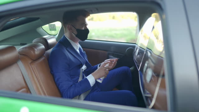 businessman with protective face mask, disinfecting hands with antiseptic at taxi - rubbing alcohol stock videos & royalty-free footage