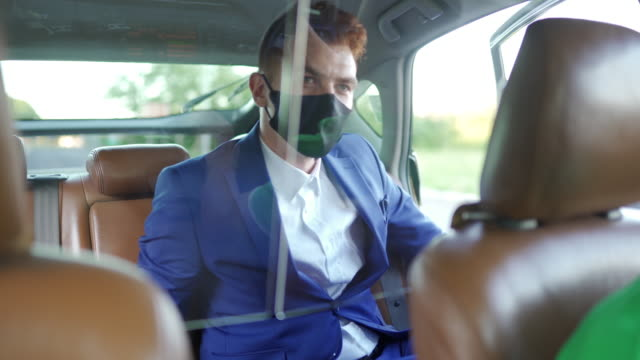 businessman with protective face mask using phone and leaving crowdsourced taxi - taxi stock videos & royalty-free footage