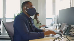 Businessman with protective face mask working at his desk