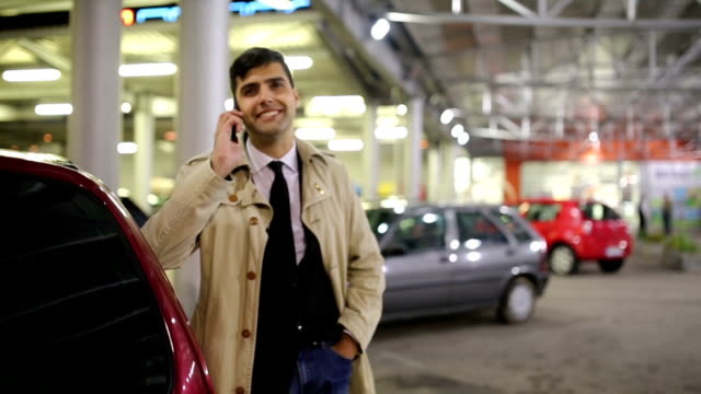businessman with smart phone at night time in parking garage - one man only stock videos & royalty-free footage