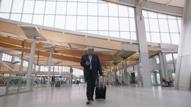 slo mo. businessman with smart phone rolls suitcase through airport terminal near entrance. - anzug stock-videos und b-roll-filmmaterial