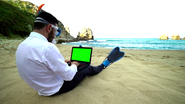 Businessman with snorkel use computer on the beach - 4K