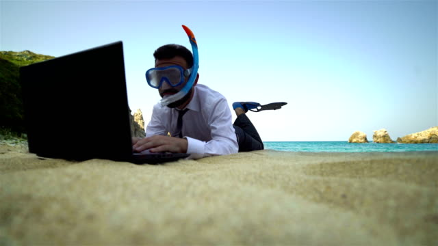 businessman with snorkel use computer on the beach - 4k - bizarre fashion stock videos and b-roll footage