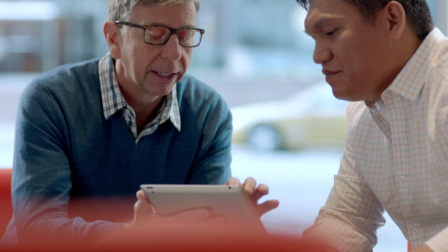 Businessman with tablet explains strategy to corporate partner (dolly shot)