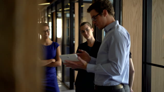 businessman with tablet pc explaining to coworkers - part of a series stock-videos und b-roll-filmmaterial