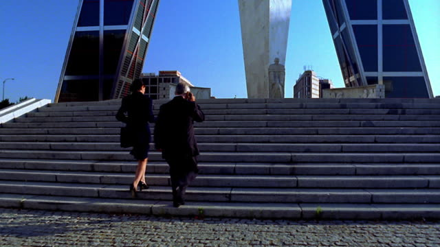 vídeos de stock e filmes b-roll de rear view businessman + woman running up stairs toward modern sculptures / madrid. - passos