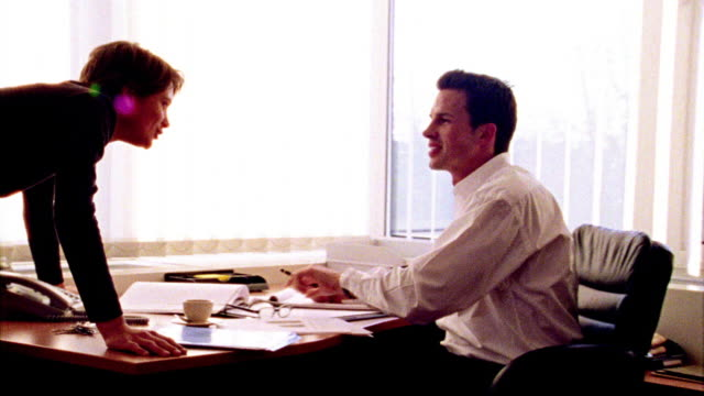 overexposed selective focus businessman + woman talking + pointing to papers on man's desk in office - overexposed video stock e b–roll