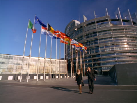stockvideo's en b-roll-footage met businessman + woman walking toward + past camera / eu parliament building in background / strasbourg, france - attaché