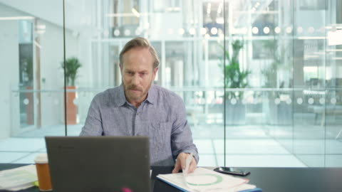 ms businessman working at desk with paperwork and laptop in board room - new business stock videos & royalty-free footage
