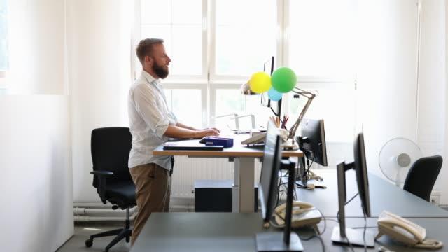 vidéos et rushes de homme d'affaires travaillant au bureau debout ergonomique - être debout