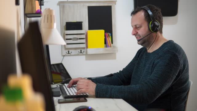 geschäftsmann arbeitet von zu hause aus, telearbeit - headset stock-videos und b-roll-filmmaterial