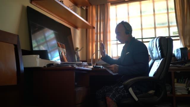 vidéos et rushes de homme d'affaires travaillant de la maison, utilisant le pantalon de pyjama tandis que participe à un appel vidéo - pantalon