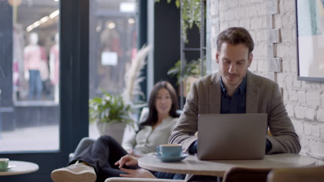 businessman working in busy cafe on laptop. man using computer devices and wireless technology. business and entrepreneurship. - smart casual stock videos & royalty-free footage