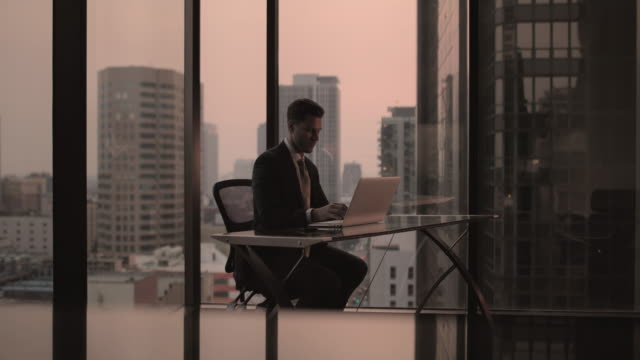 vidéos et rushes de businessman working in executive office in a skyscraper - costume complet