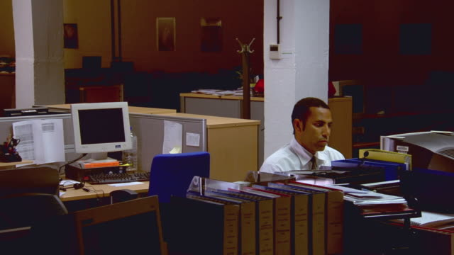 MS Businessman working late in empty office, then security guard walks up and talks to him / London, England