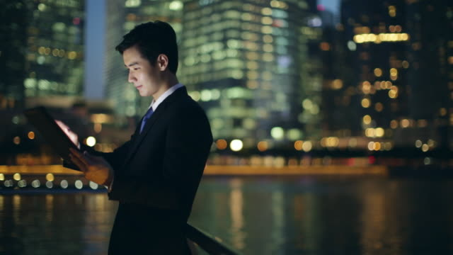 ms businessman working on a digital tablet at night. - standing stock videos & royalty-free footage