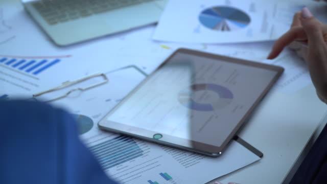 vidéos et rushes de homme d'affaires travaillant sur une tablette numérique dans le bureau - analyser