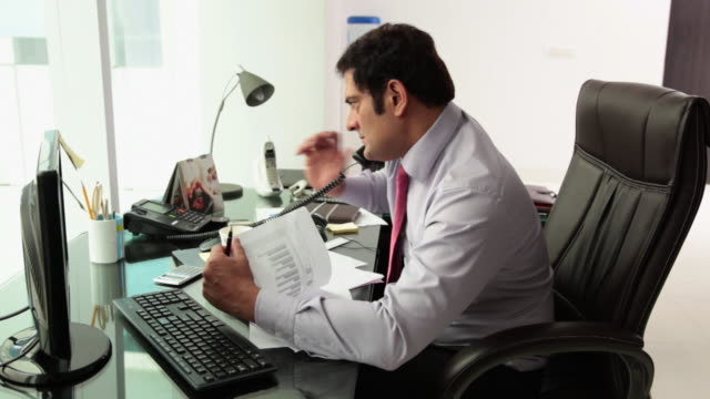 Businessman working on a laptop and talking on a landline phone