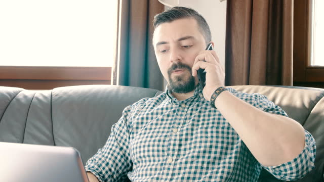 商人從家裡的筆記本電腦和電話交談 - 回答 個影片檔及 b 捲影像